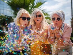three older ladies blowing confetti