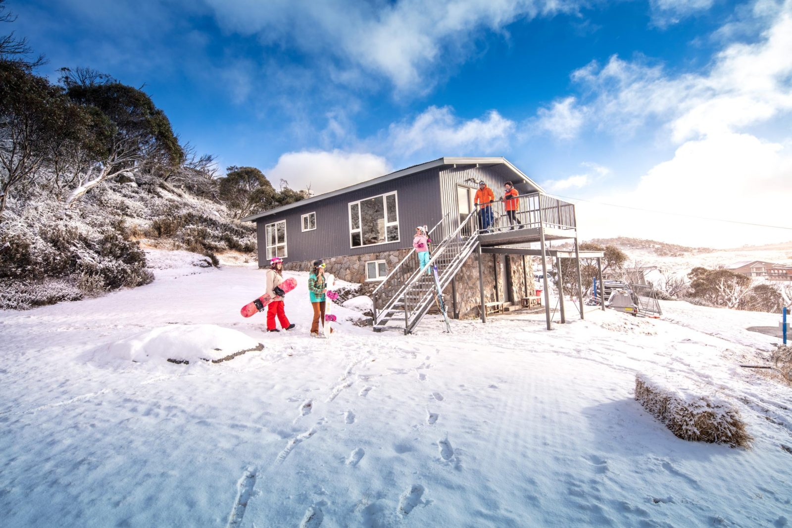 A family in the snow outside Numbananga Lodge, Kosciuszko National Park