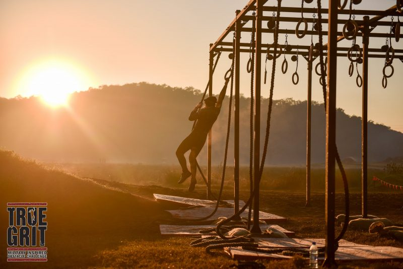 Athlete swings through rings at sunrise, sun peeking over mountains