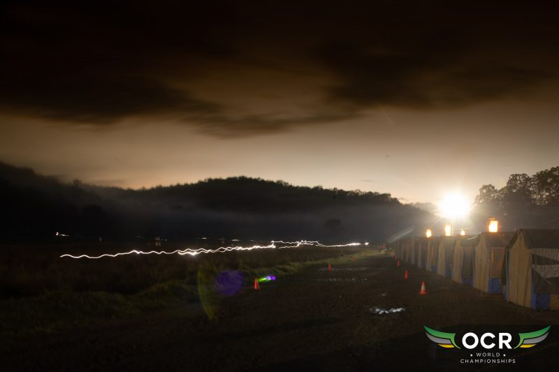 Long exposure showing headlights of athletes taking on course beside tents for pit stops.