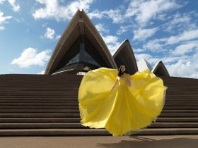 A woman in a flowy yellow dress stands on the steps of the Sydney Opera House