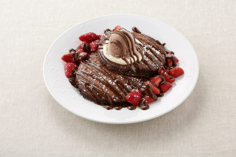 Chocolate pancakes covered with cream, chocolate ice cream and strawberries, with chocolate sauce