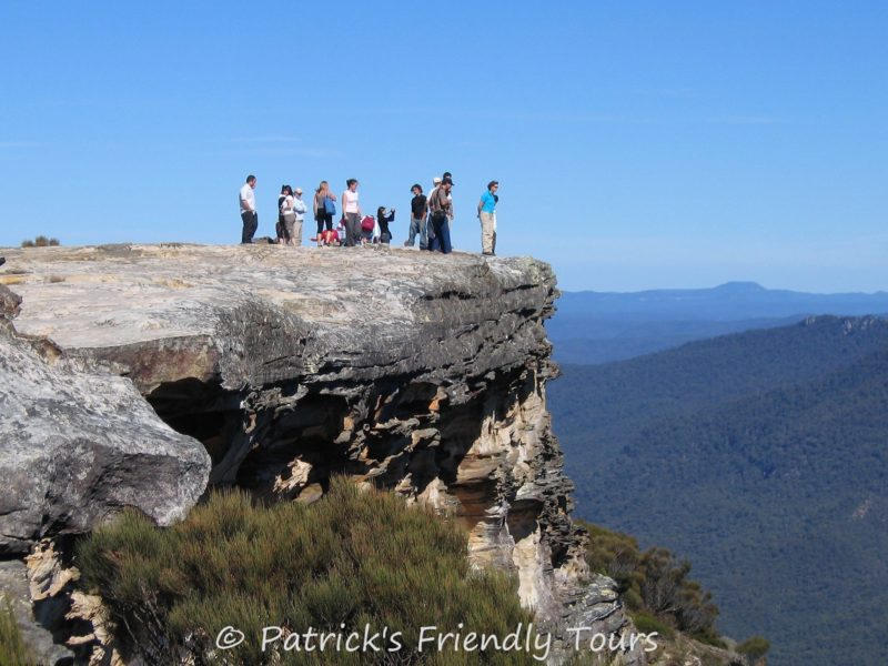 People standing on the cliff edge, gazing down into Jamison valley view below.