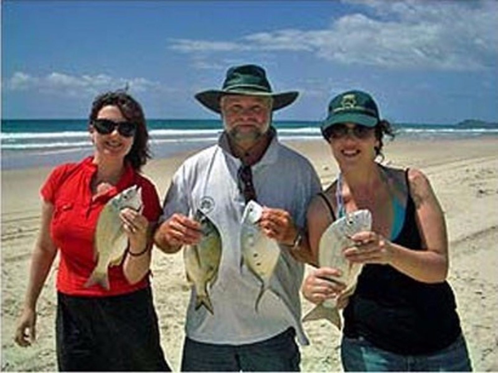 Paul on beach with two ladies holding up fish