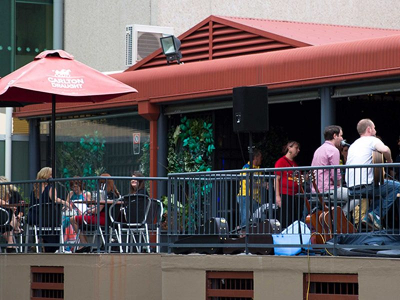 Outdoor veranda filled with performers and patrons
