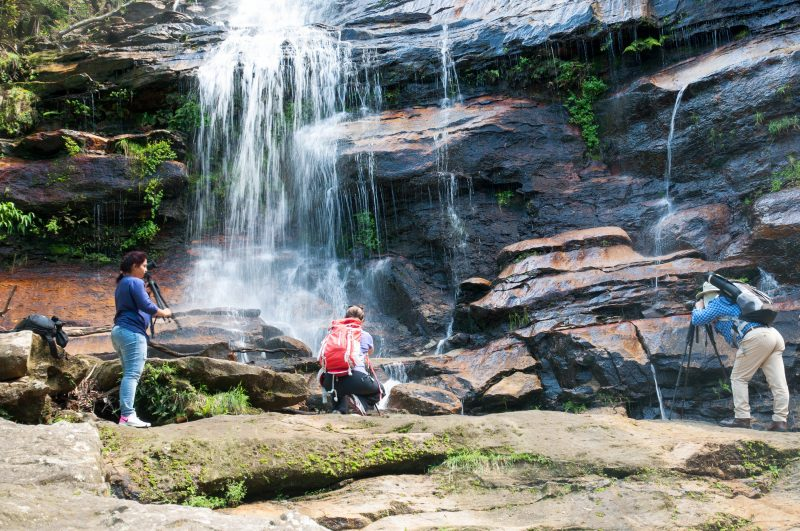 People at the base of a waterfall taking photos