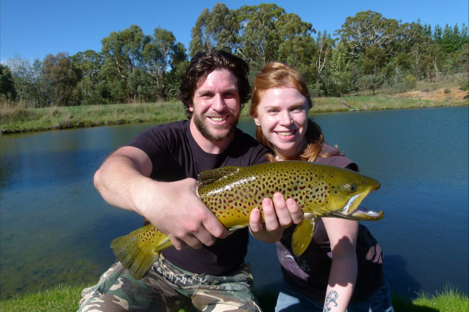 Young couple holding big brown trout