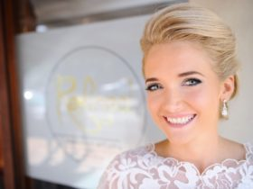 Bride smiles, showing off her makeup done by Refined Makeup Artistry Studio