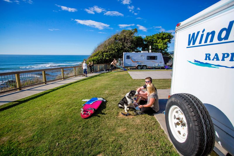 Couple and dog taking in the beach views at Reflections Holiday Parks Bonny Hills