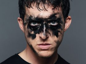 A man with black paint on his face stares intensely at the camera