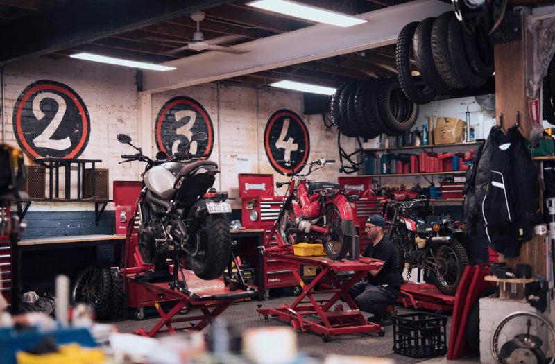 Man working on his motorcycle at the Rising Sun Workshop