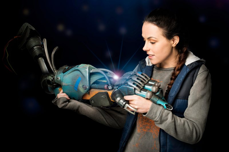 girl holding the hand of a big robot