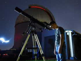 Young man looking through telescope
