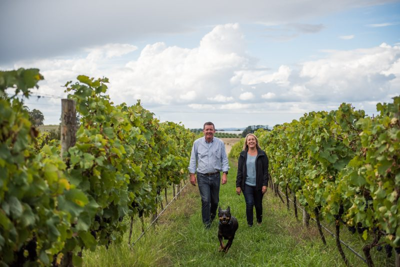 James & Chrissy Robson walking in the vineyard with their dog Jerry