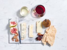 A tablescape of artisans cheeses and wine glasses viewed from above