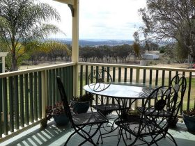 Patio with outdoor setting in foreground with view of Inverell in background
