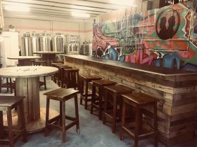 Wooden tables and bar with brewing tanks and graffiti mural behind