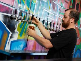 Bar tender pouring beer from line of taps