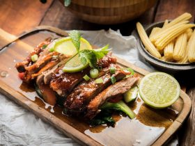 Roast duck on a plate with lime wedges