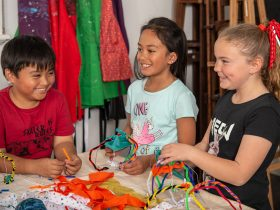 Children building baskets from wire, fabric and other materials