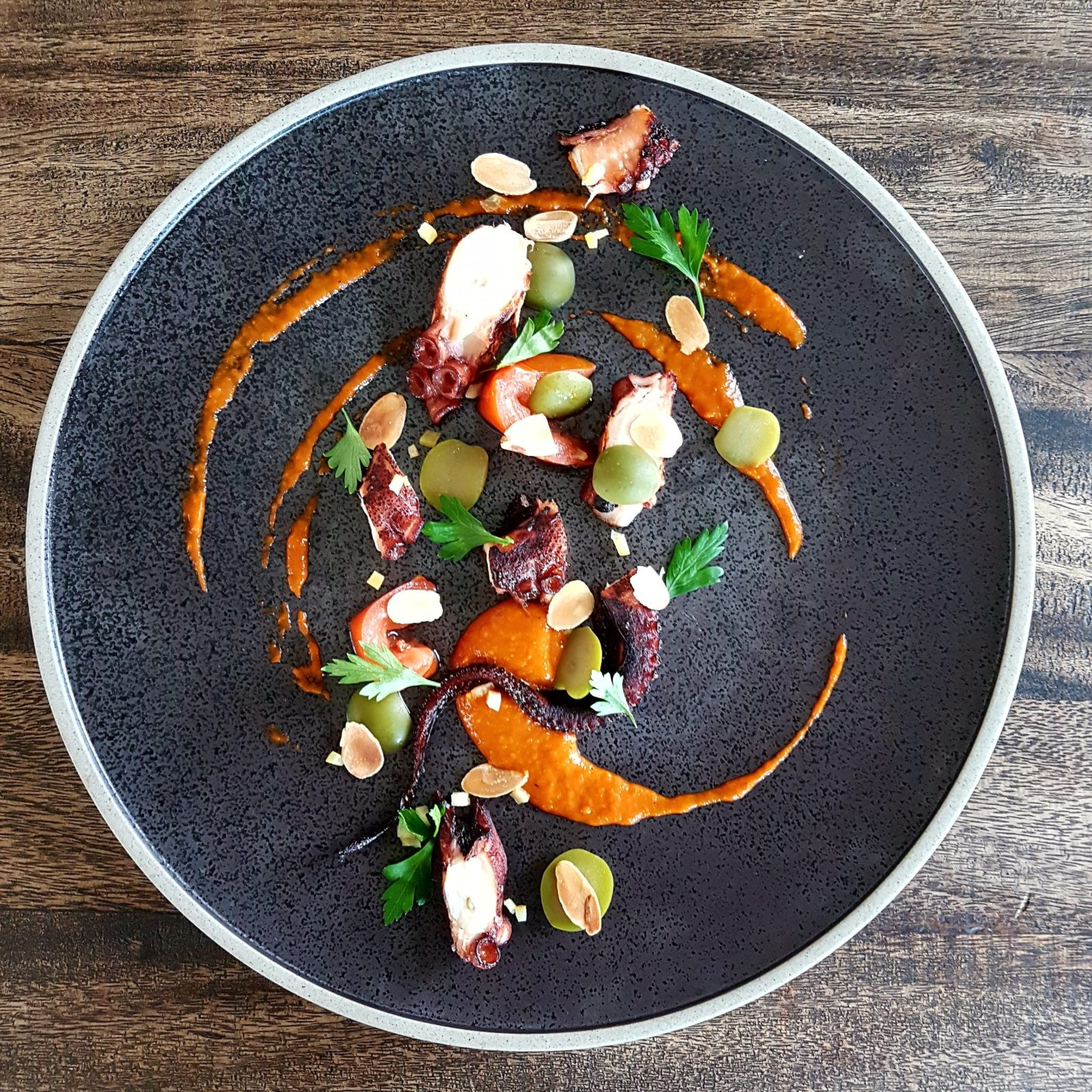 Char-grilled octopus with chilli jam, almonds, parsley and lemon