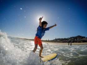 This young girls has her thumbs up to her surf lesson