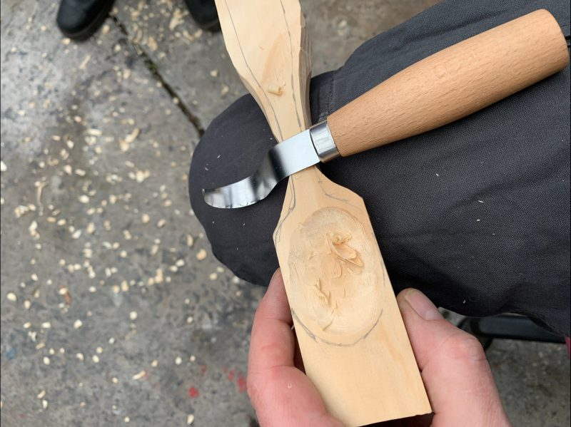 Shows carving a wooden spoon