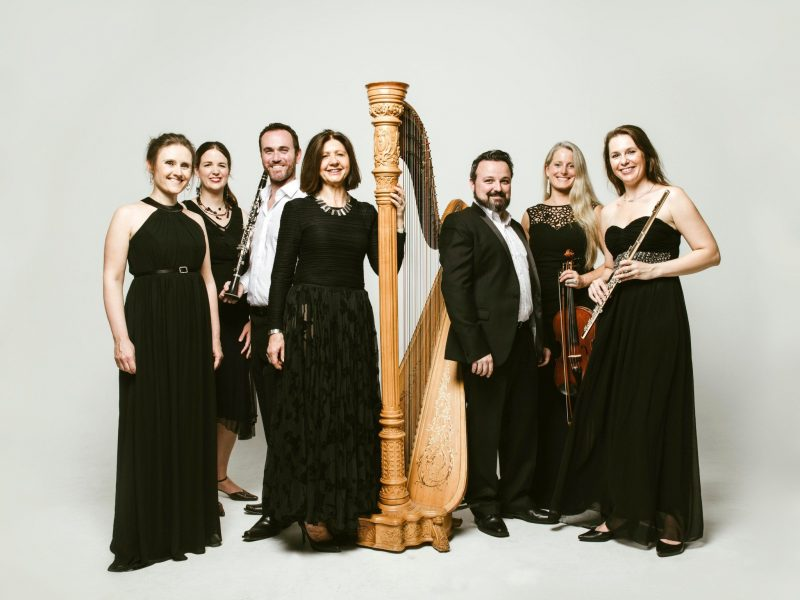 Seven musicans in evening wear holding their instruments