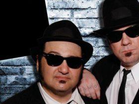 Two men wearing hat and dark sunnies