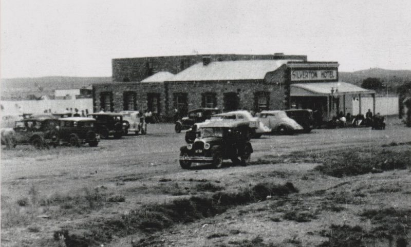 Old cars driving by the Silverton Hotel