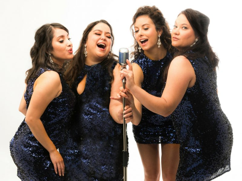 The four Sapphires in blue sequin dresses singing into a microphone