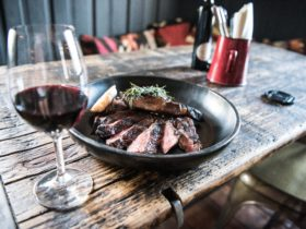 Plate of steak and a glass of red wine on a rustic table at the Sir George