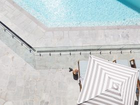 Overhead shot of grey and white striped umbrellas, turquoise pool and crazy pave