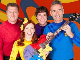 The new Wiggles holding a guitar signed by new and old members
