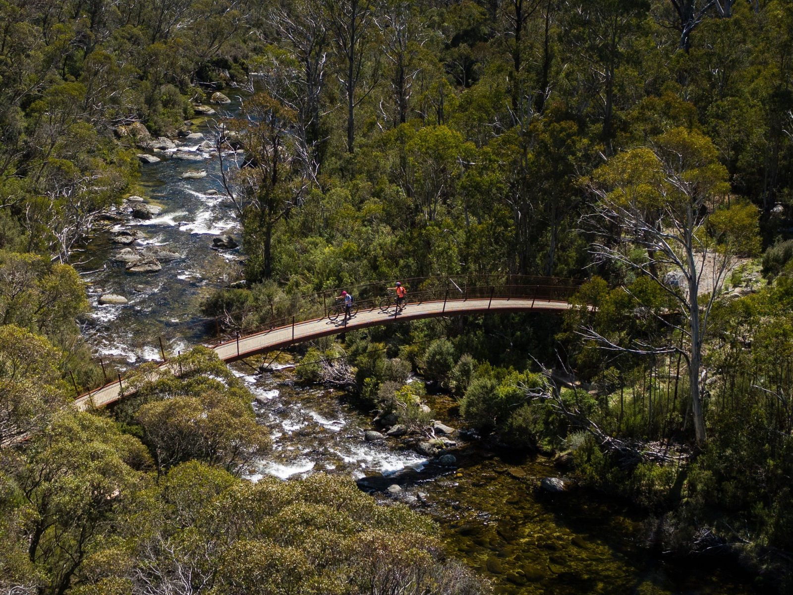 Aerial view of two bike riders crossing a bridge on Thredbo Valley track, Kosciuszko National Park