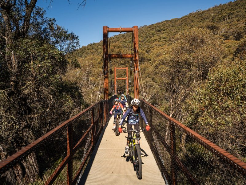 A family bike rides across a suspension bridge along Thredbo Valley track, Kosciuszko National Park