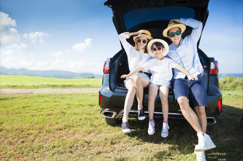 Family relaxing in the boot of a vehicle
