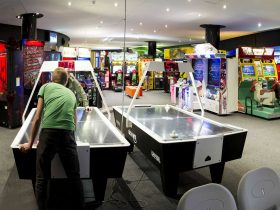 Men playing Air hockey tables and arcade games behind them