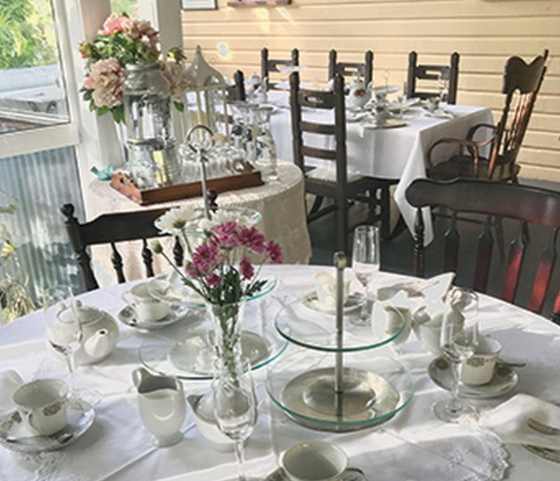 High Teas setting on table with flower arrangement and fine china