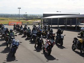 Motorcyclists waiting in a group next to race track