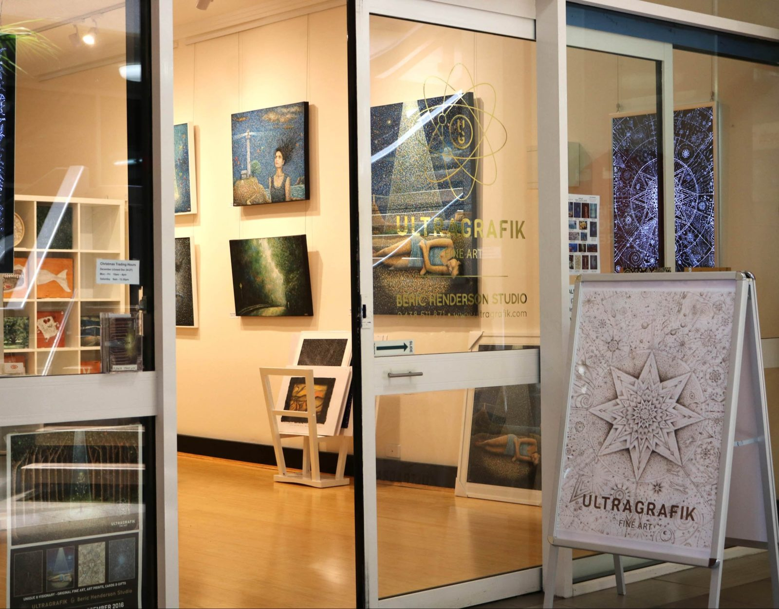 Front window and entrance of Ultragrafik, showing paintings inside.