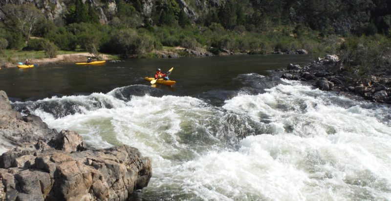 A nervous kayaker lines up on a rapid during the Walking Rivers Snow River, two other Kayaks waiting