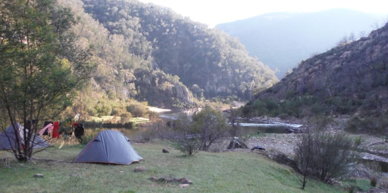A tent is in the foreground on the edge of the Snowy River, beautiful mountains in the background