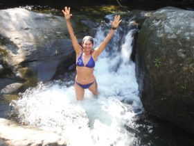 A female standing arms out stretched in a natural river spa below a waterfall between large rocks