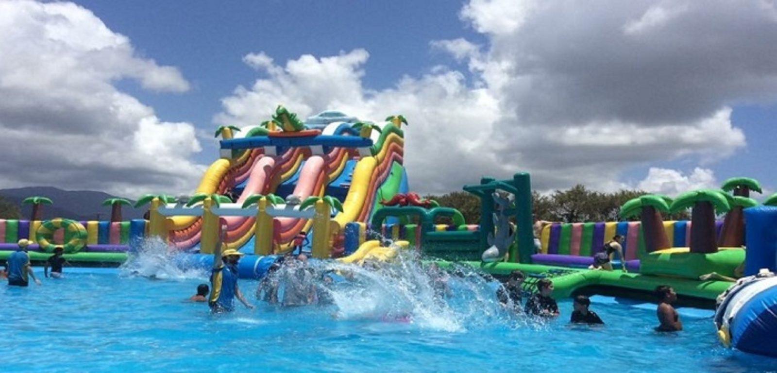 Kids splashing and having fun on inflatable slides at Water Wonderland