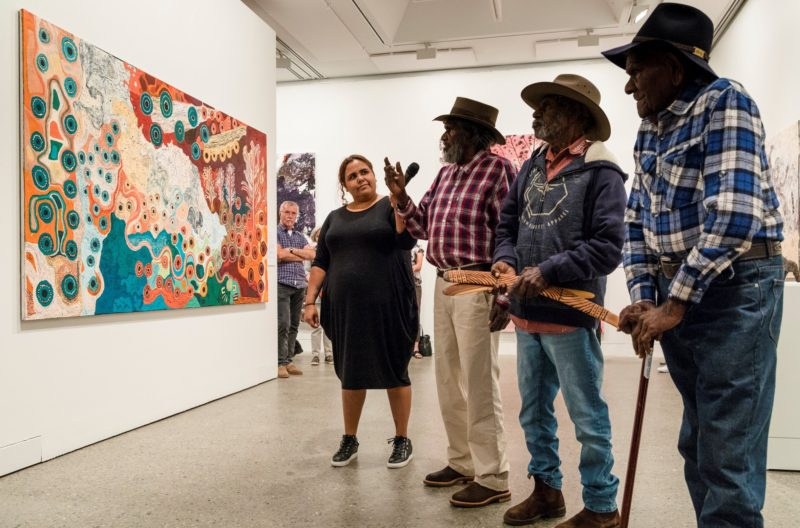 Image of Indigenous artists viewing their artwork in the Regional Gallery.