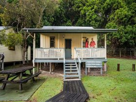 Hammonds Cottage, front exterior with visitors on the verandah, Woody Head, Bundjalung National Park