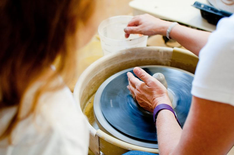 A white woman's hand on pottery with the wheel circulating around