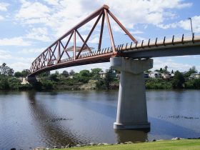 Large orange bridge over Nepean River on sunny day