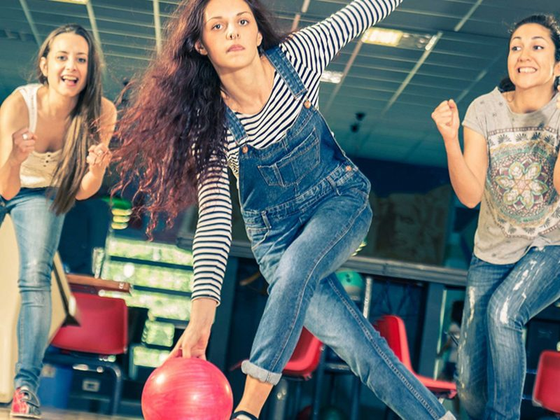 Young women bowling surrounded by friends cheering